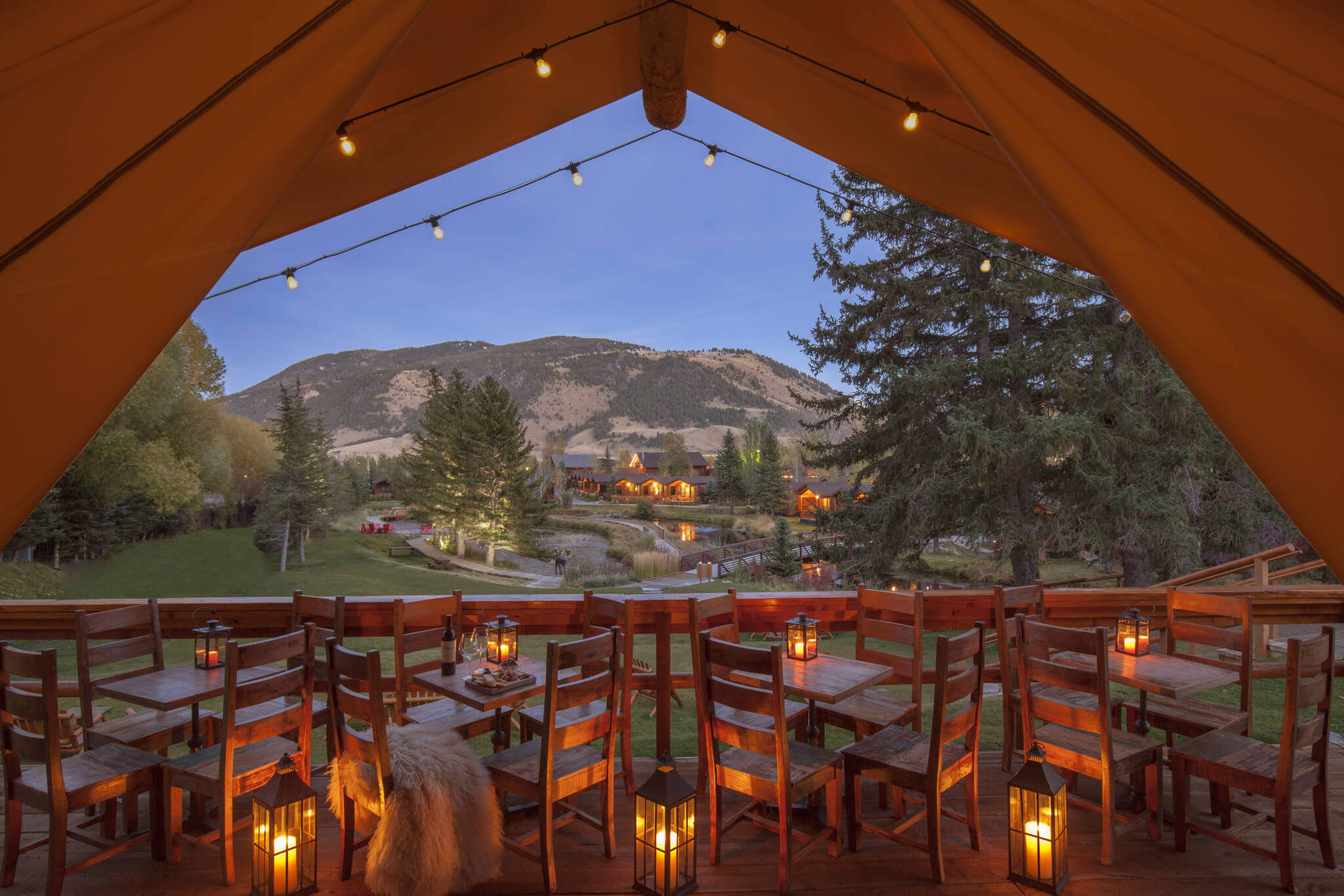 wooden tables under a canvas tent outside with lantern lights on them overlooking Rustic Inn
