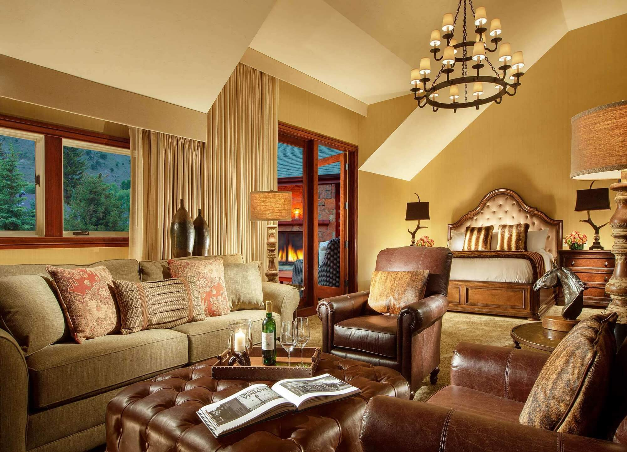 luxury hotel room with leather couches, king sized bed and outdoor fireplace