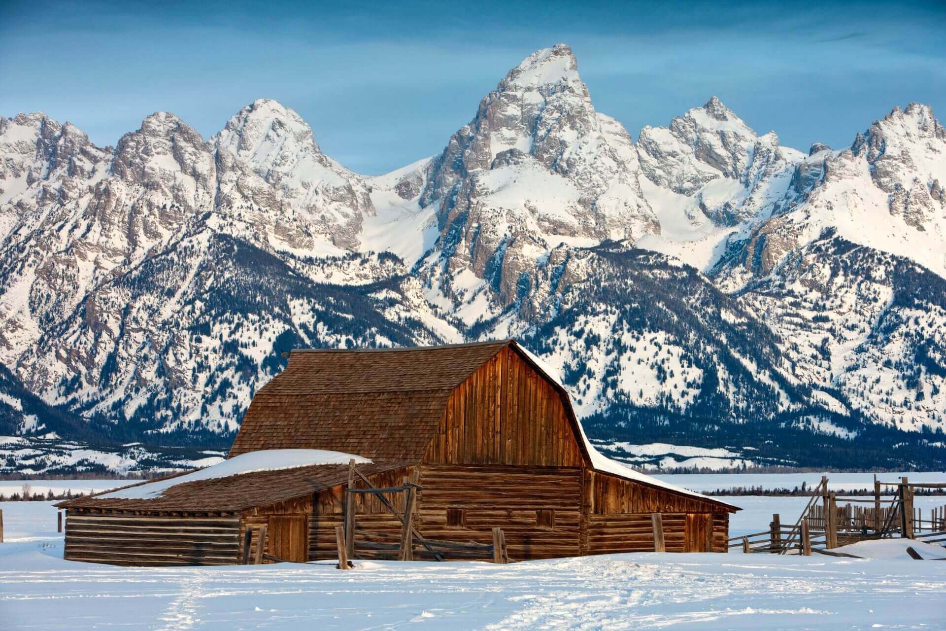 Wooden barn in winter with moutain backdrop