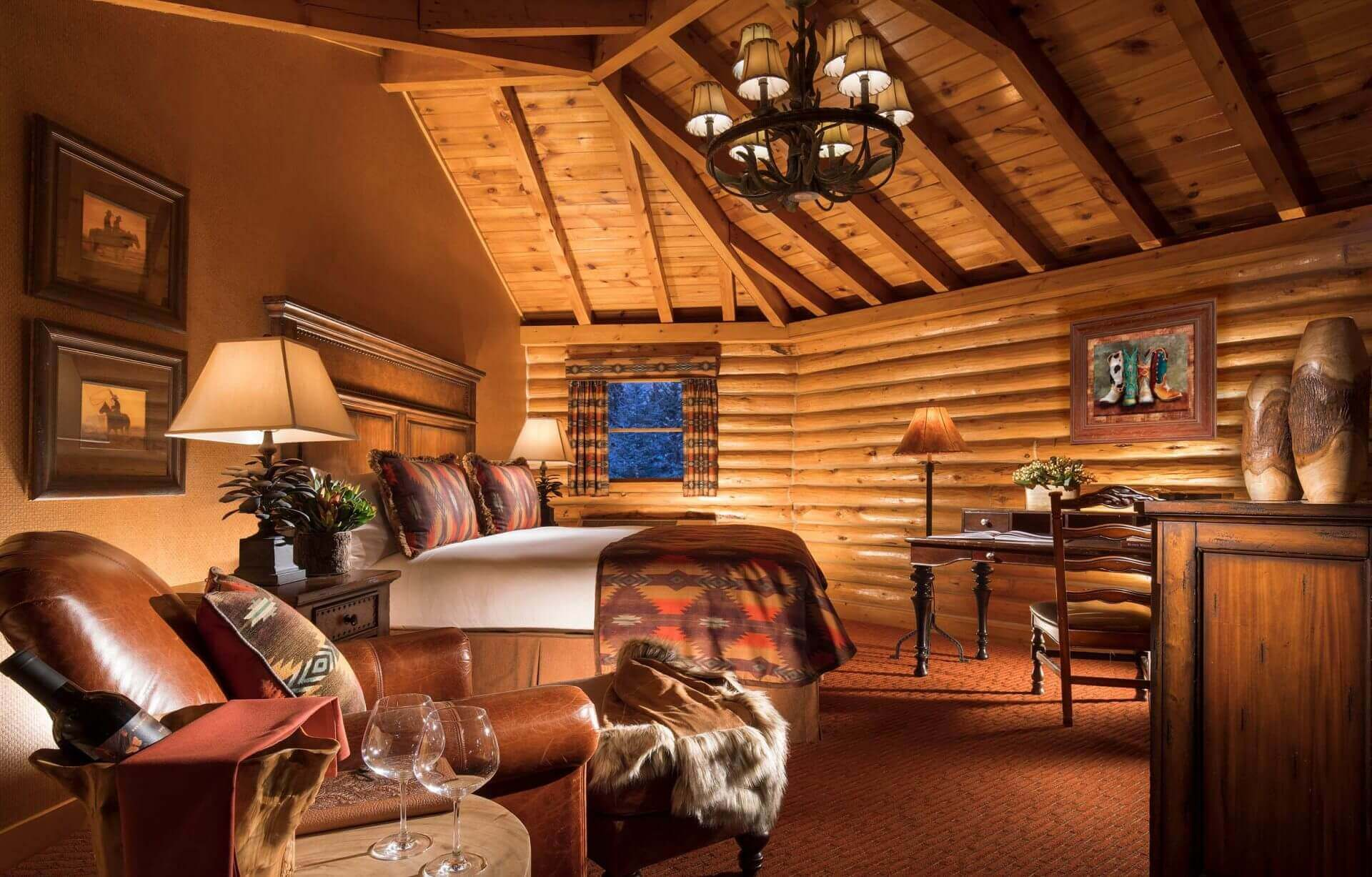 luxury hotel cabin with king bed and wooden log ceiling and walls