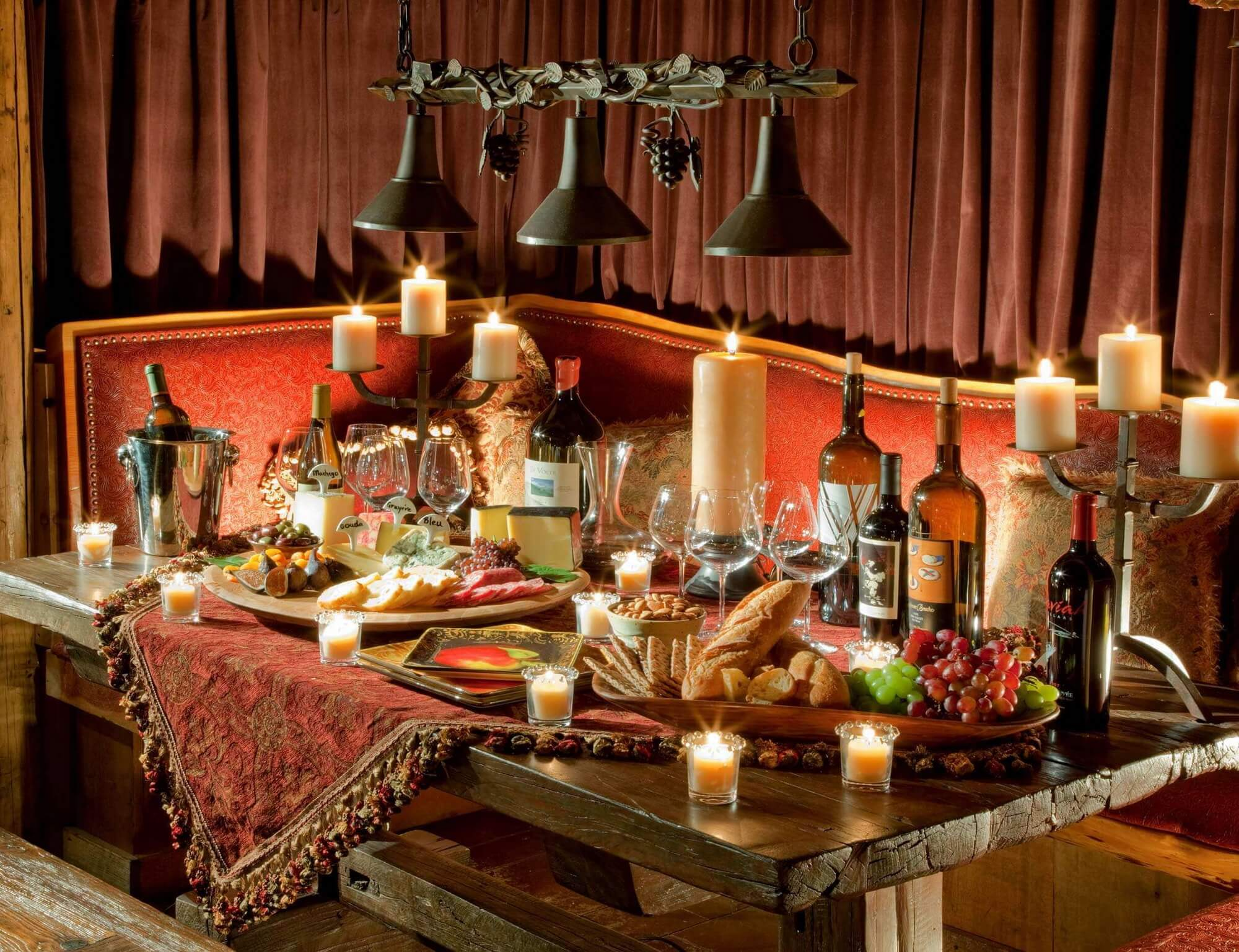 dining table with several bottles of wine, candles and fruit and cheese platters