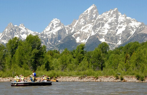 group of people on scenic float trip on river with mountain in background