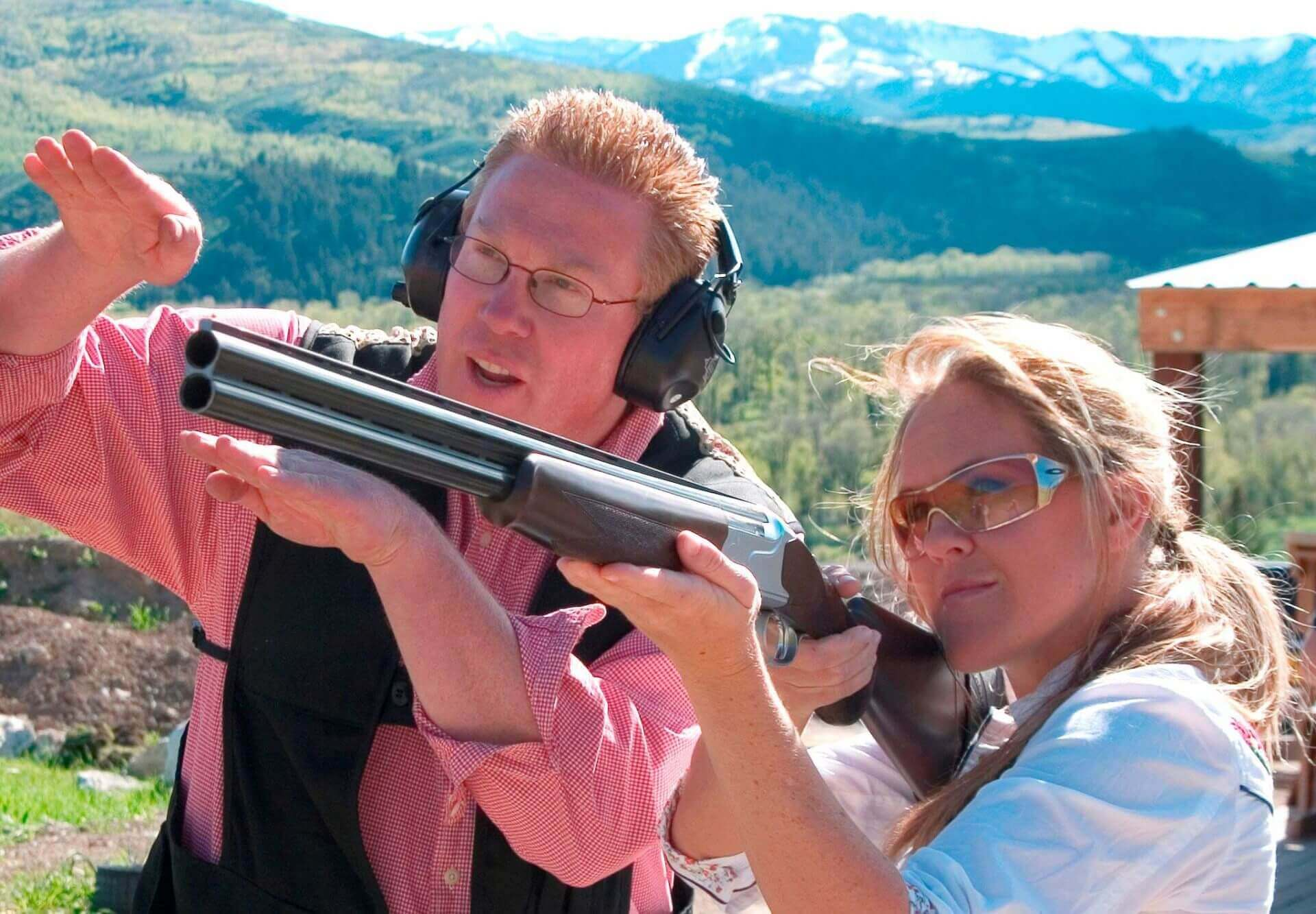 male instructor teaching a woman how to shoot a rifle