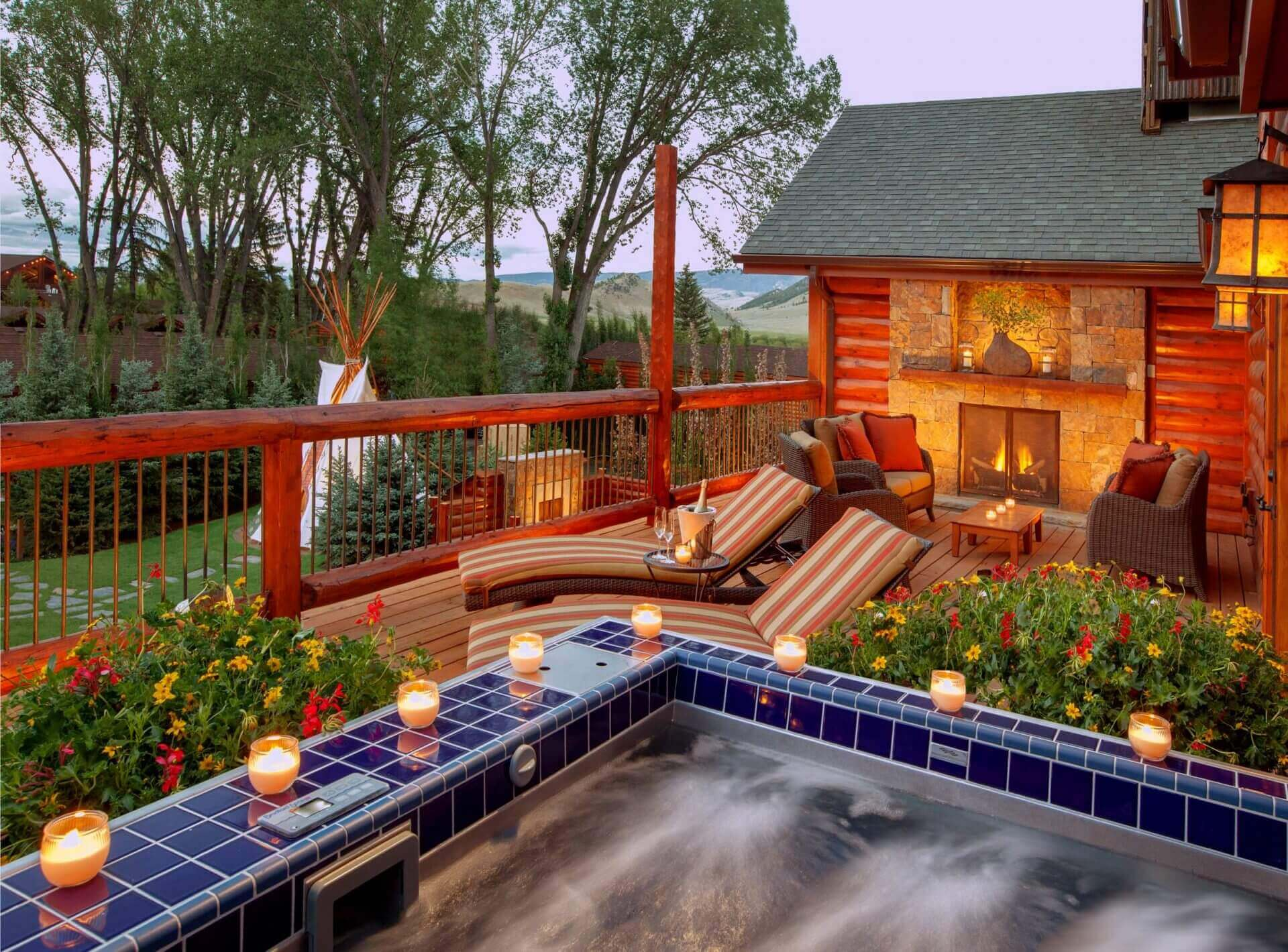 outdoor hot tub lined with candles next to a deck with a fireplace