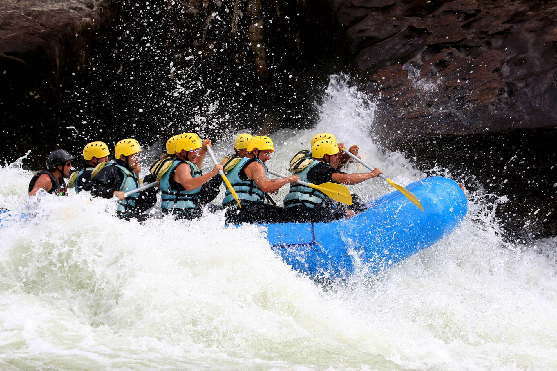 group of people on blue raft paddling through rapids on river