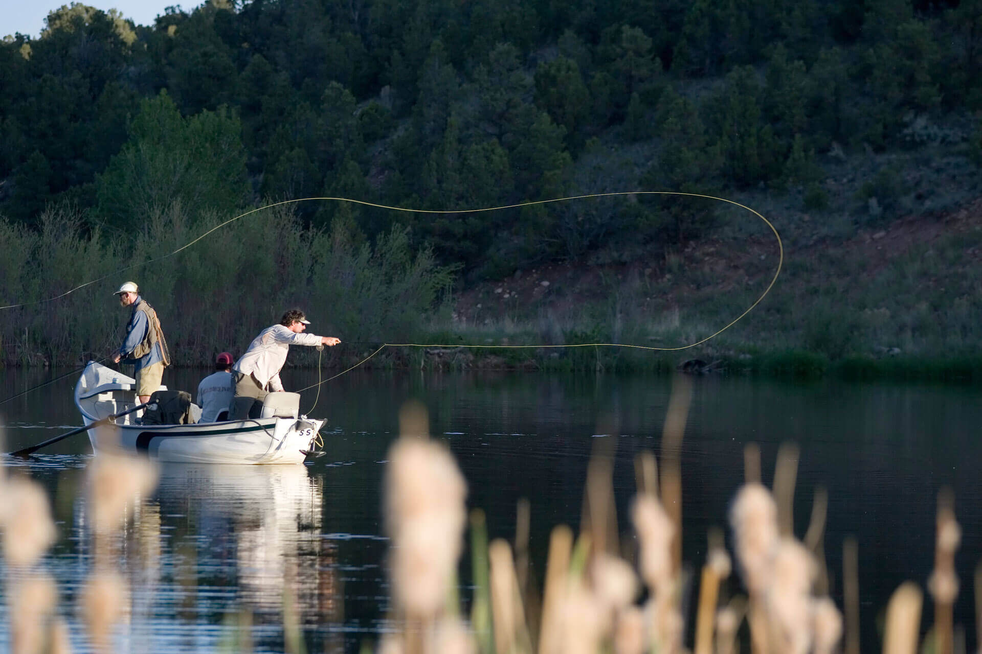 man on a boat in river casting off while fly fishing