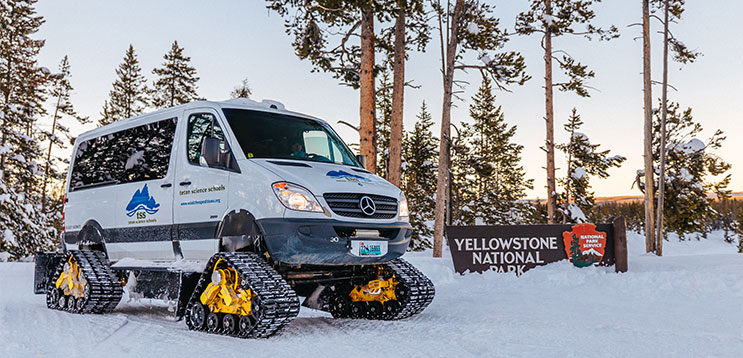 snowcoach van parked by Yellowstone sign in winter