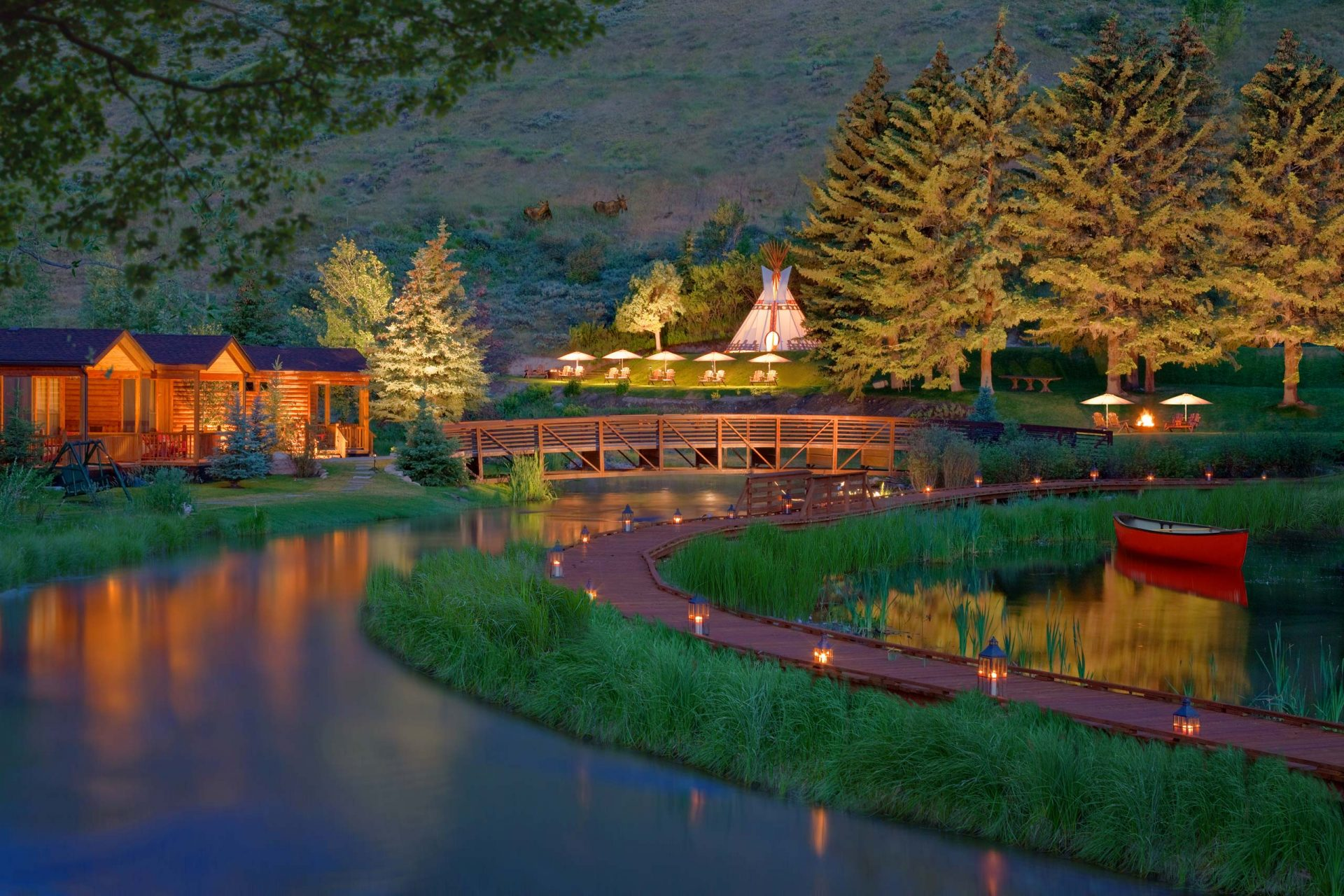 evening view of wood bridge, cabins, river and trees with moose on hill in background