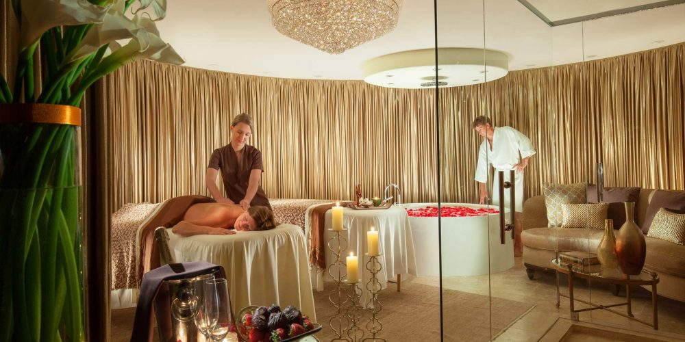 spa room with female getting massage and male filling bath tub